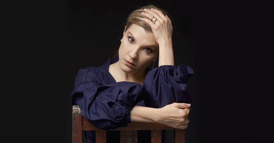 Mujer posa en fotografía tomándose su cabello