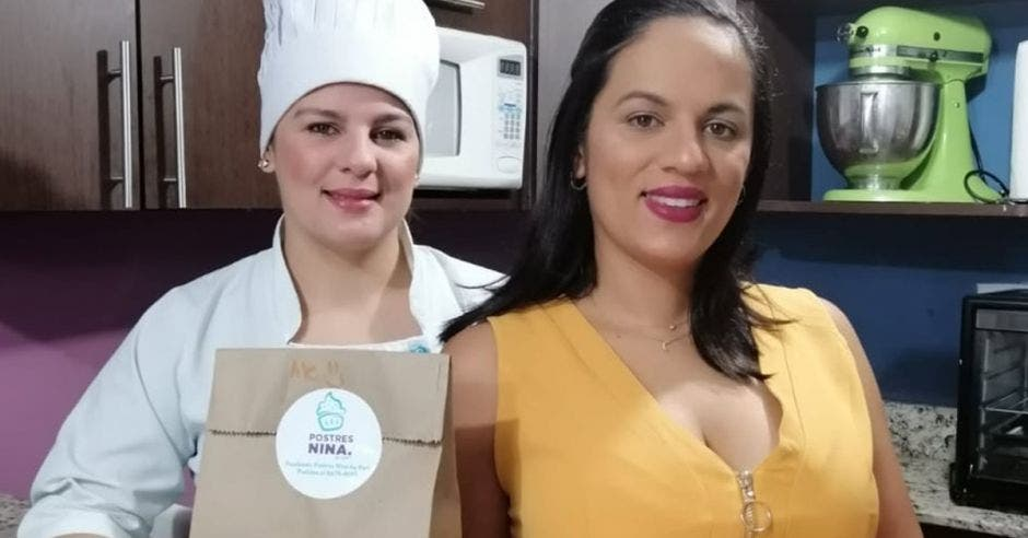 Emprendedoras posan, una con un sombrero de chef