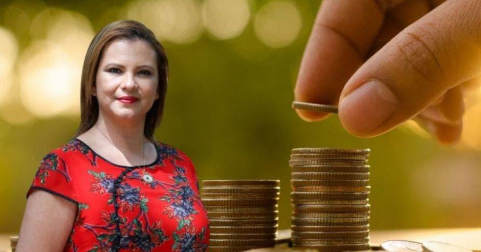 Carmen Chan, jefa de Nueva República frente a arte de persona colocando monedas en columna
