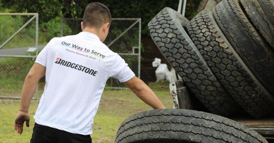 """Vemos a una persona de espaldas con una camisa blanca que dice """"Bridgestone"""" a la par de un montón de llantas."""