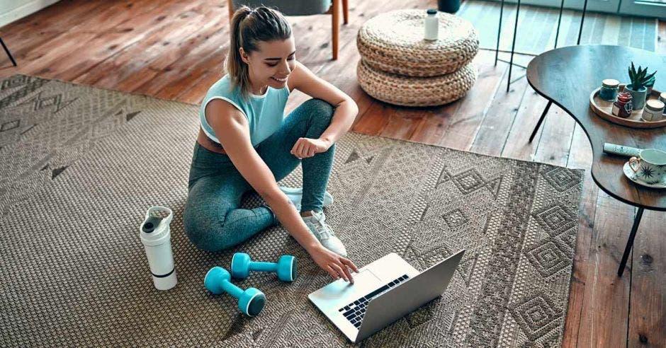 Una mujer haciendo ejercicio frente a una computadora