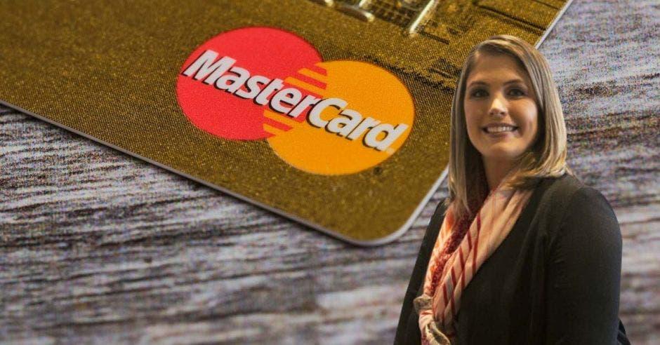 Mujer posa frente a tarjeta de Mastercard