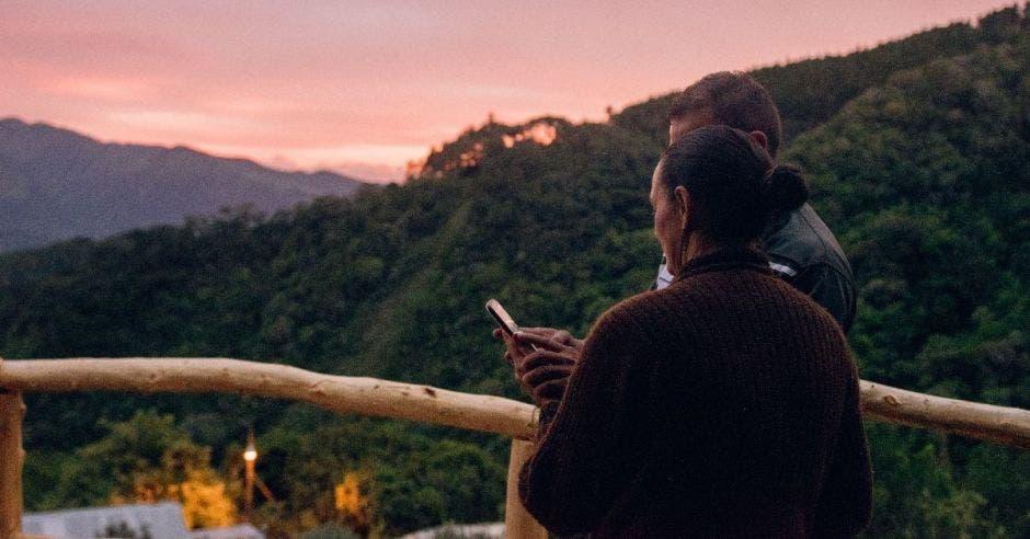 Un hombre muestra algo a una mujer en un celular