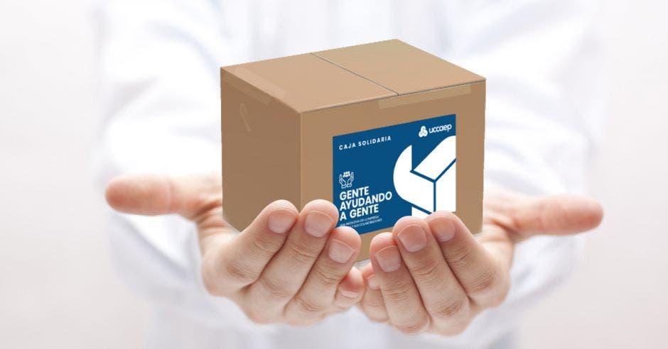 Vemos unas manos abiertas sosteniendo una caja