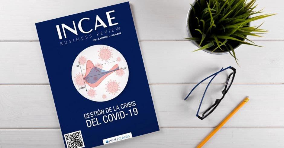 Vemos la edición del INCAE Business Review en un escritorio junto con anteojos y lápices.
