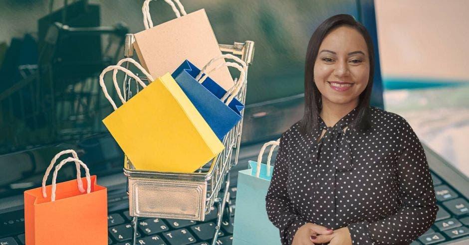 Mujer posa frente a bolsas de compras