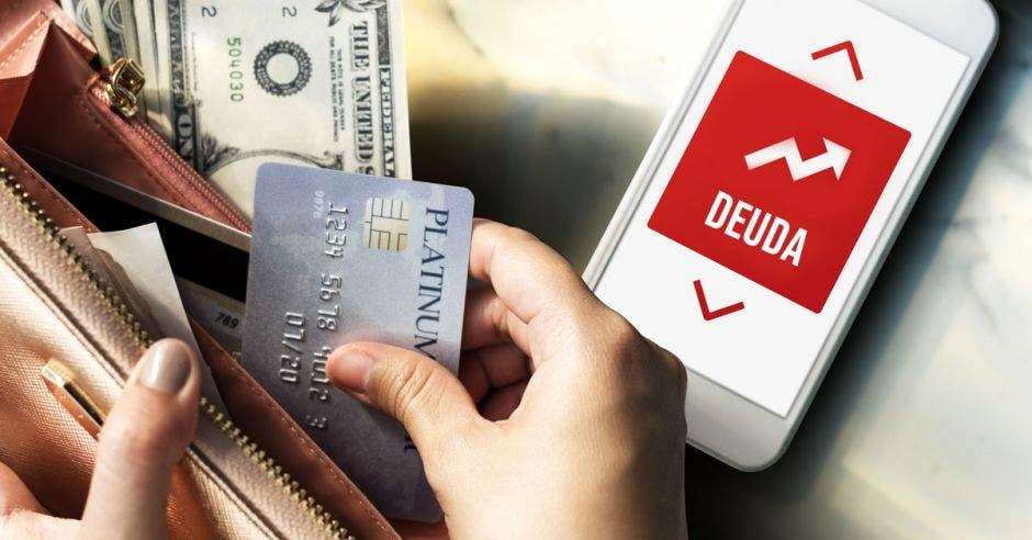 Mano saca tarjetas mientras celular alerta de deuda