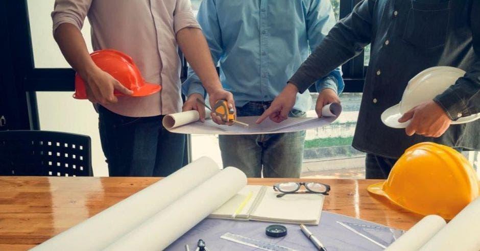Un grupo de personas manipula un plano topográfico