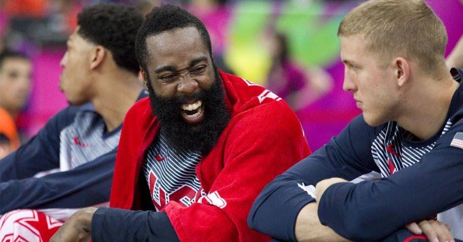 Un hombre con barba sonríe mientras conversa con otro hombre sentado en frente suyo