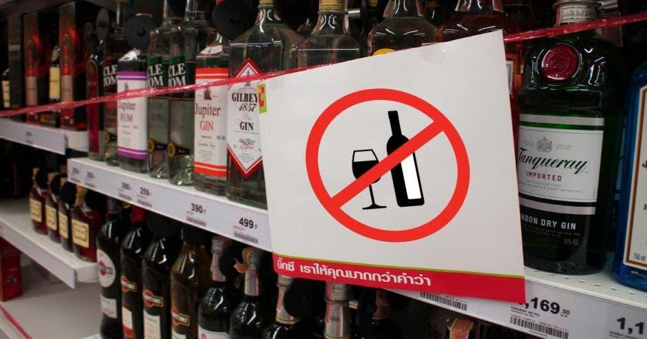 Vemos botellas en una góndola con cinta encima.