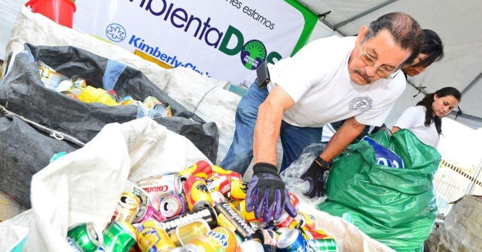 un hombre recolecta latas de cerveza en una bolsa de reciclaje