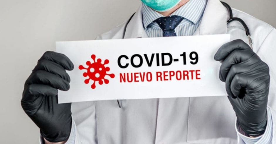 Persona sosteniendo un papel con reporte de nuevos casos de Covid-19