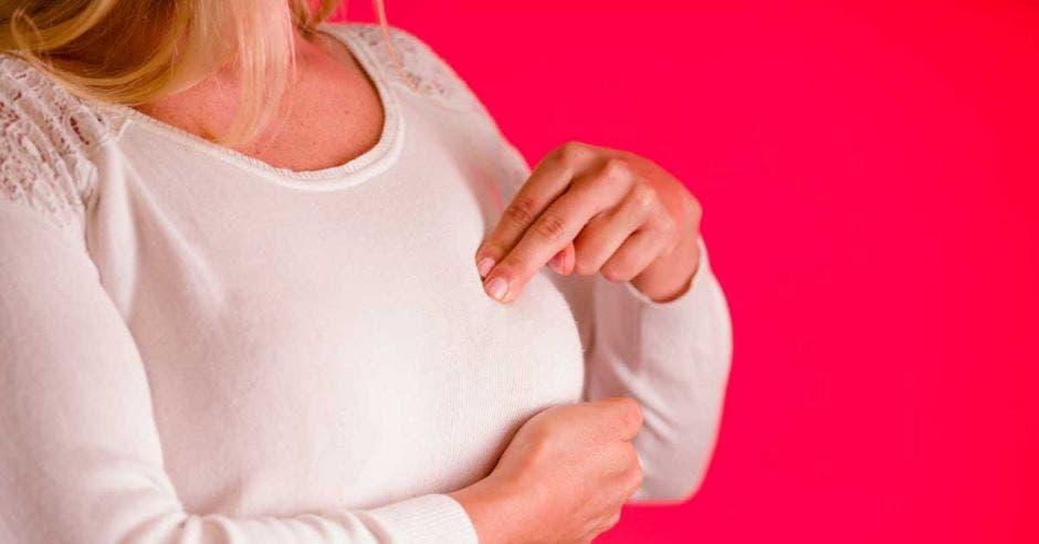 Mujer haciéndose el autoexamen de mama