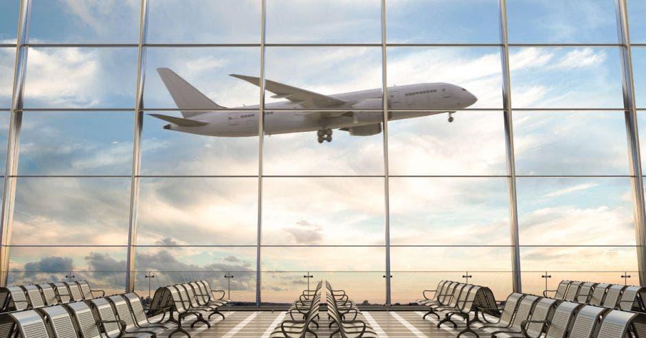 Vemos un avión detrás de un ventanal en un aeropuerto