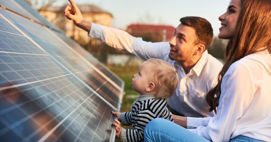 Una pareja y su hijo manipulan un panel solar