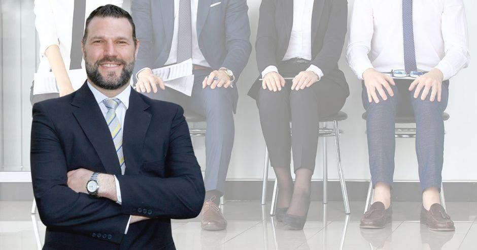 Daniel Suchar de traje con personas sentadas de fondo