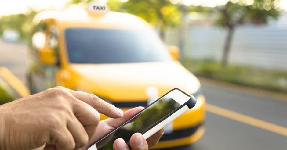 Vemos a alguien con un celular y detrás un taxi