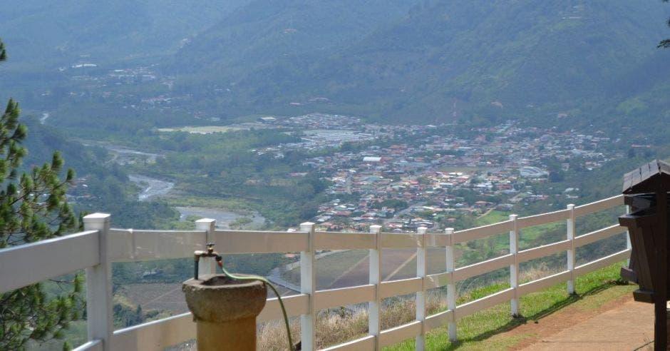 Un mirador en la parte alta de una montaña, separado por una baranda blanca