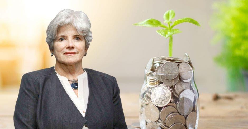Mujer con traje posa frente a jarrón con monedas