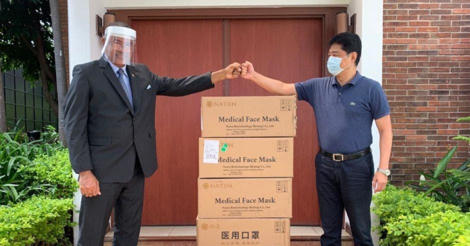 Personas con mascarilla presentando donaciones