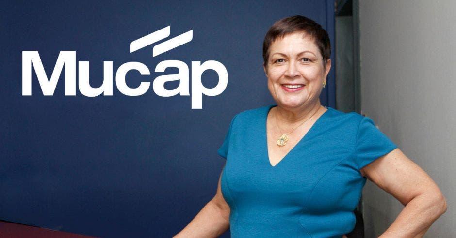 Mujer posa frente a logo de Mucap