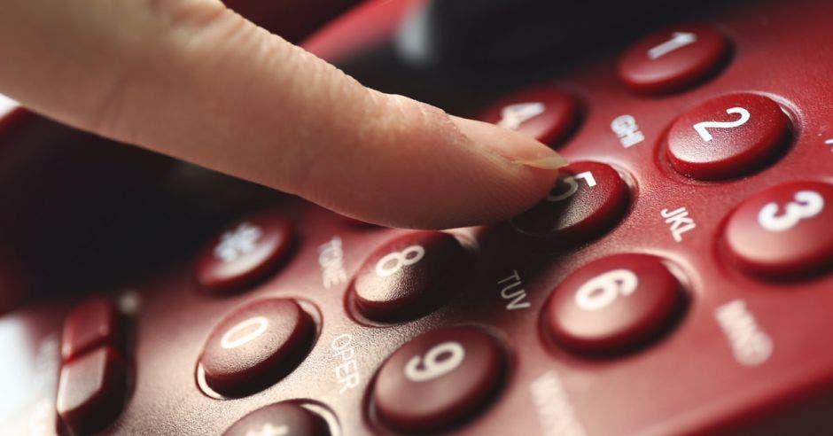 Vemos un dedo apretando botones de un teléfono.