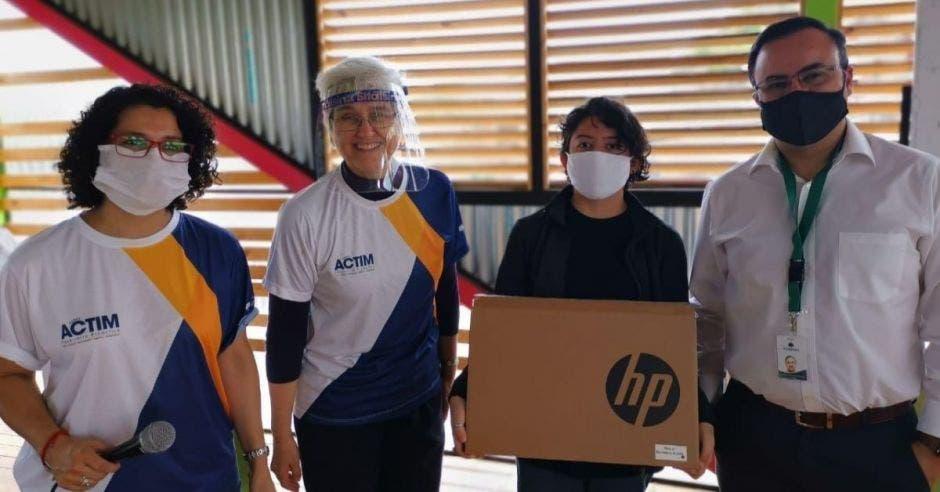 Un grupo de personas recibe equipo de computación marca HP