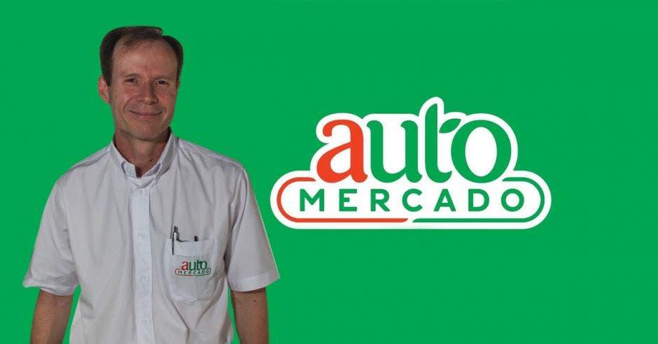 Hombre sonriente frente a logo de AutoMercado