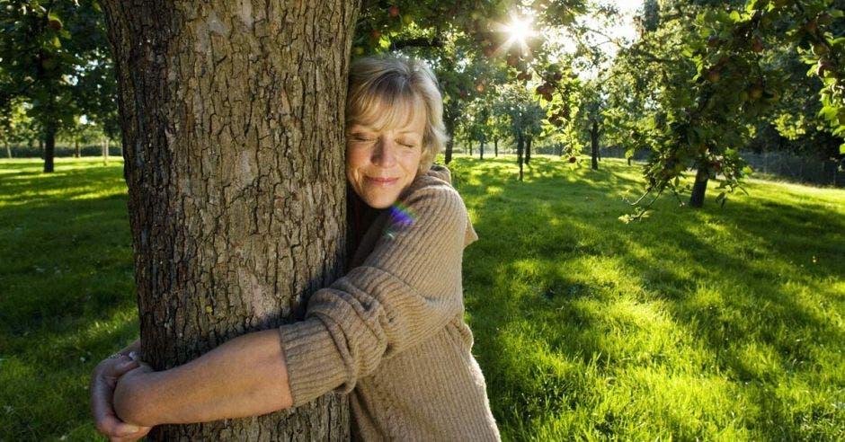 Una señora está abrazando a un árbol