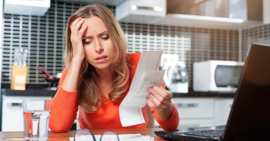 Vemos a una mujer  frustrada con una factura.