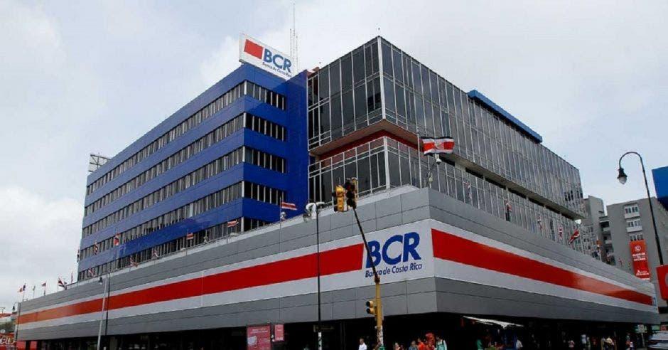 Fachada de un amplio edificio gris con detalles en banco, azul y rojo