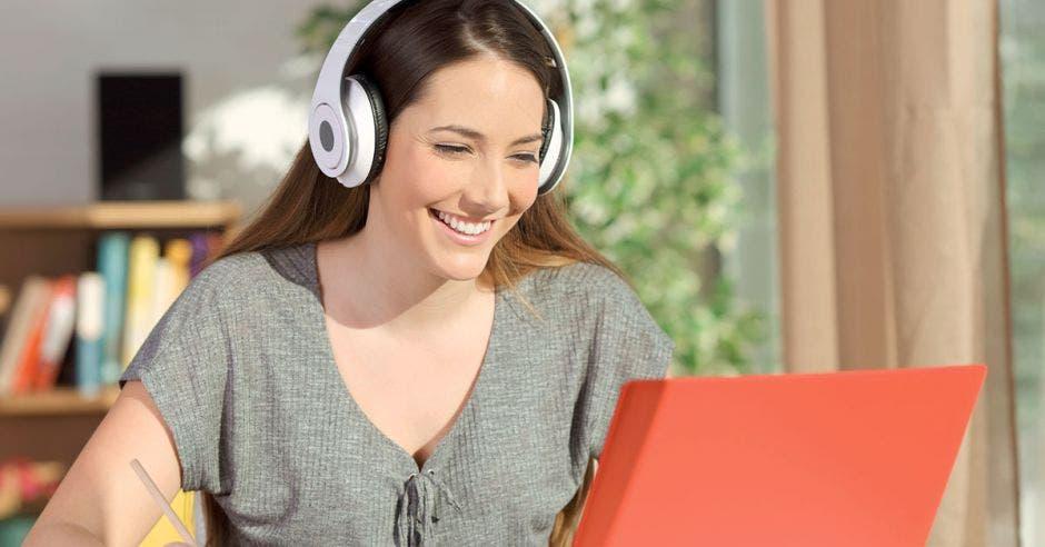 Una mujer con audífonos, sonriente frente a una computadora