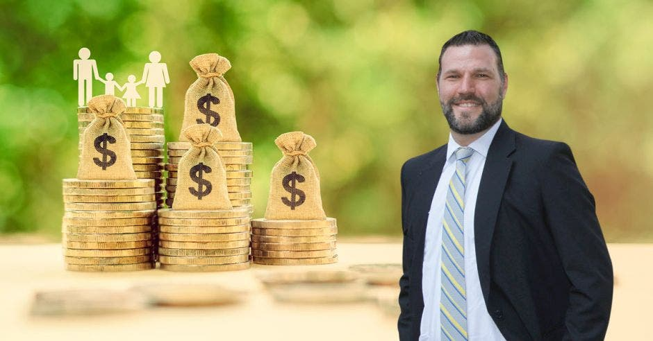 Hombre de traje sonriente frente a arte de monedas y bolsas