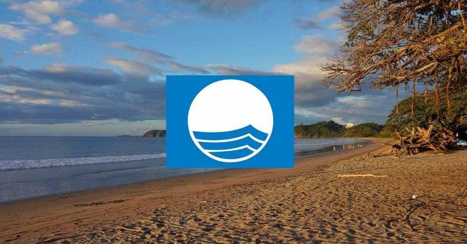 El logo de bandera azul sobre una playa al atardecer