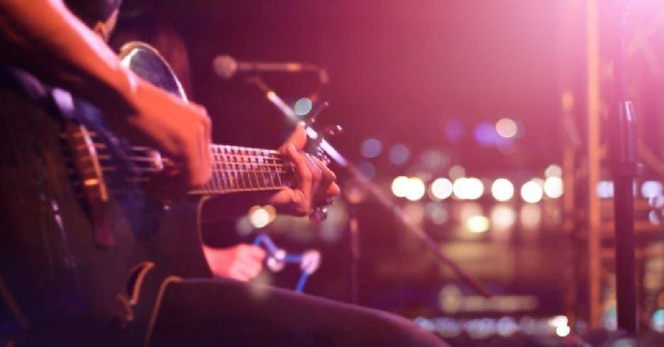 Persona tocando guitarra en evento
