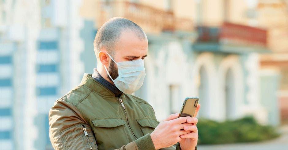 Persona con mascarilla utilizando celular