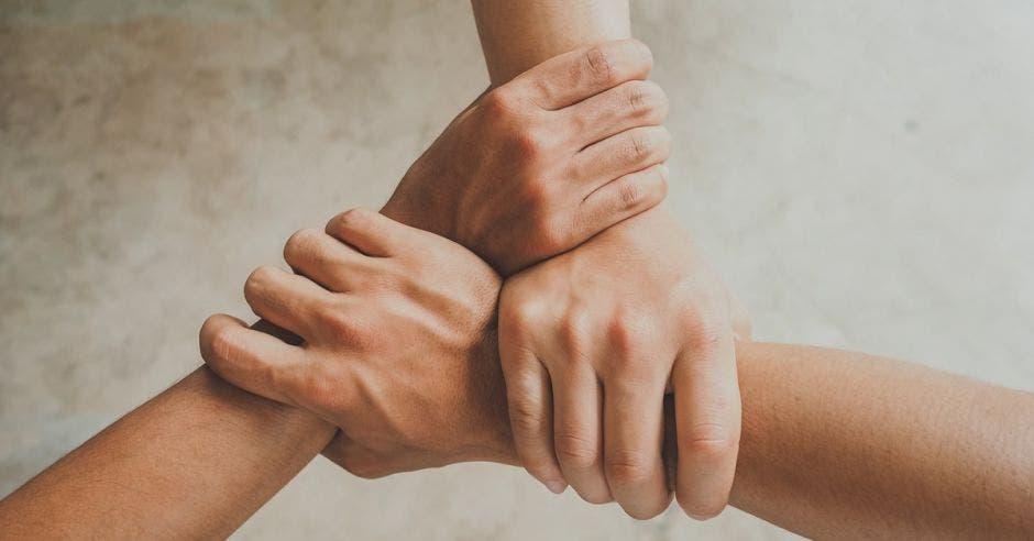 Tres personas agarrándose de las manos en señal de unión