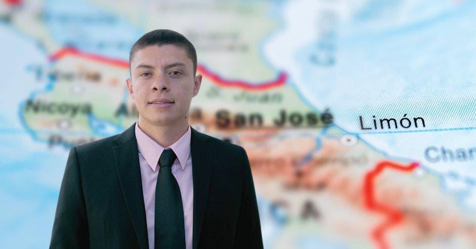 Un hombre de saco y corbata posa frente a un mapa de Limón, Costa Rica