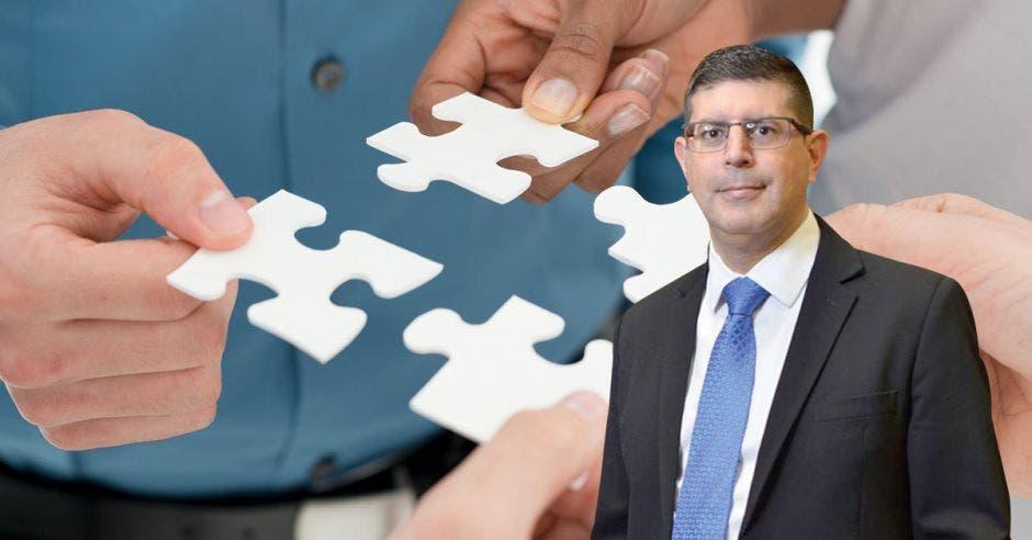 Vemos una imagen de piezas de rompecabezas blancas uniéndose y enfrente el gerente del Banco Nacional.