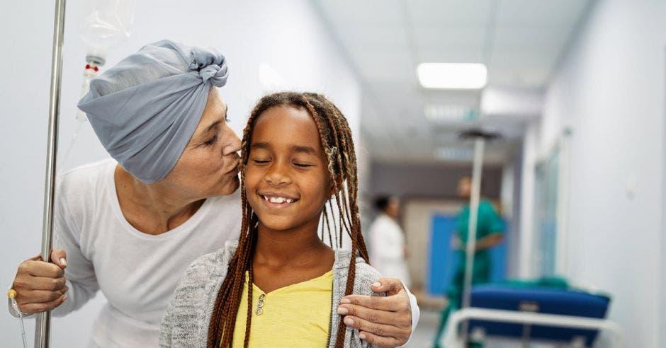 Una paciente de cáncer abraza a su nieta en un hospital.