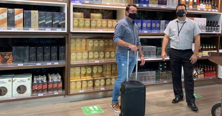 Un hombre con una valija de rodines en una tienda duty-free