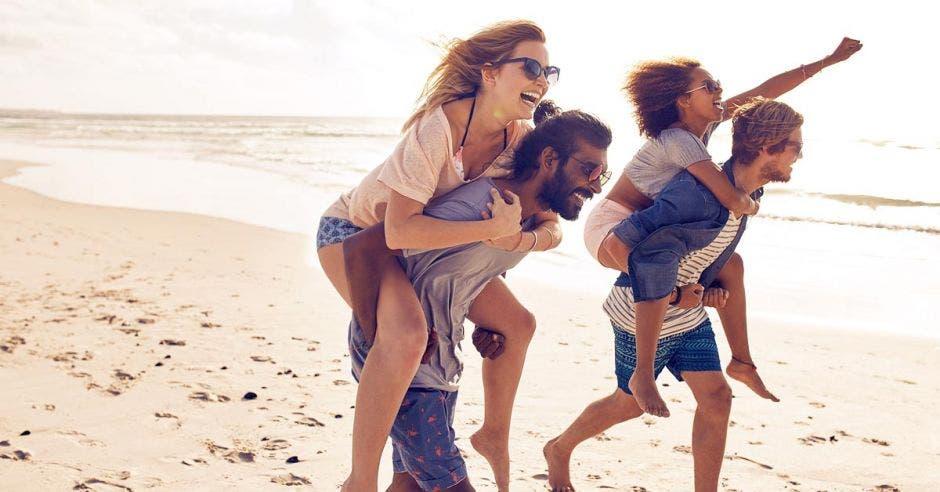 Dos parejas corren a lo largo de la playa