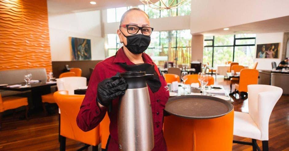 Vemos a una mesera con mascarilla sosteniendo café