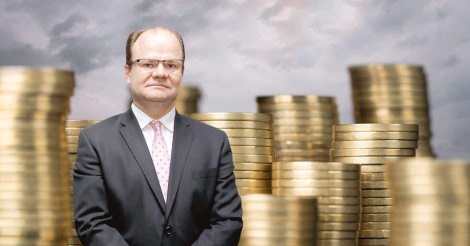 Hombre de traje frente a arte de monedas de fondo