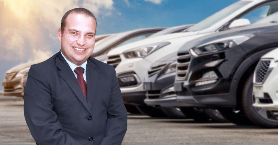 Hombre de traje frente a autos parqueados