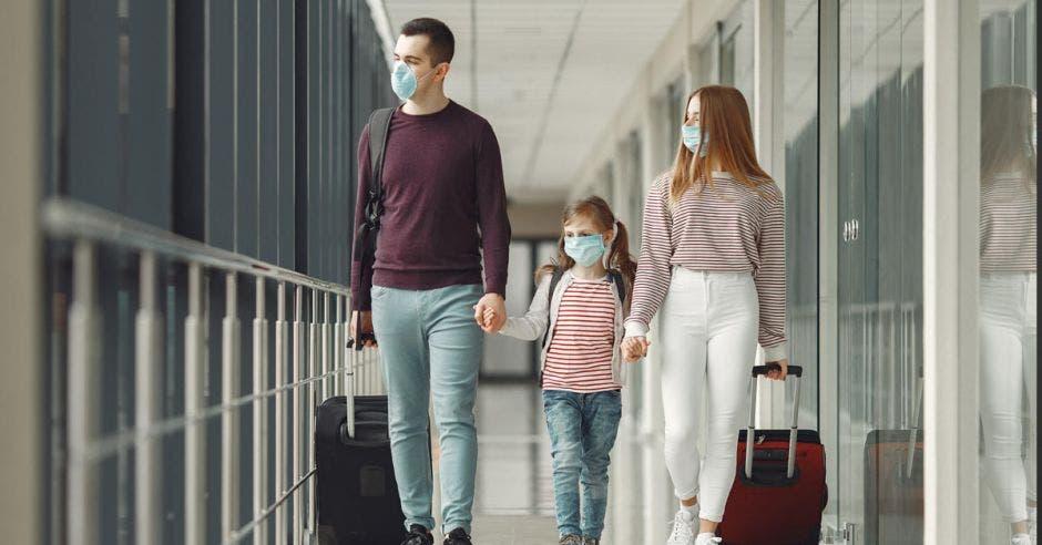 Una familia con cubrebocas traslada equipaje