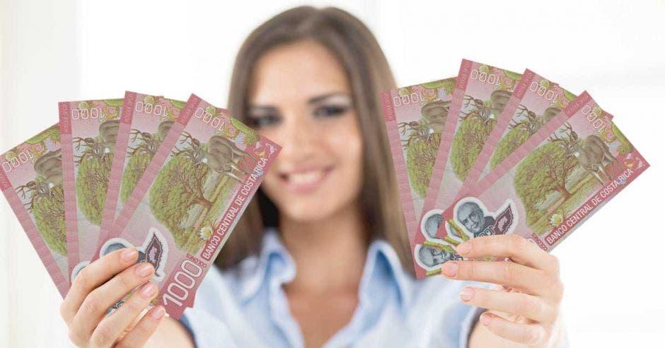 Billetes de mil colones en mano de mujer