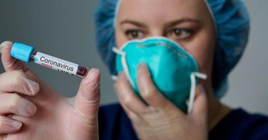 Mujer viendo prueba de sangre mientras tiene mascarilla