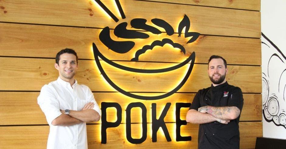 Un hombre con amisa blanca y otro con camisa negra posan frente a un letrero que dice Poke