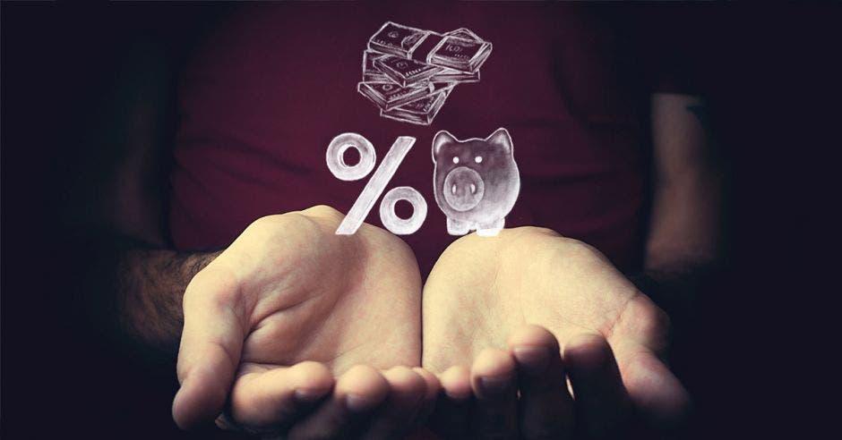 Persona extiende manos con arte de porcentaje, alcancía y billetes